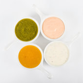 Bowls of dipping sauces. Rose sauce, mint raita, coriander sauce and mango chutney. Shot from above on a white background.