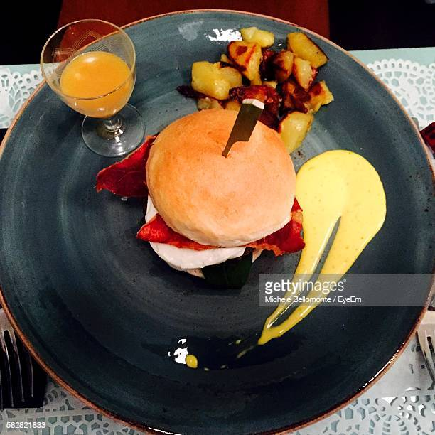 Direct Above Shot Of Served Burger And Fried Potato With Orange Juice In Plate