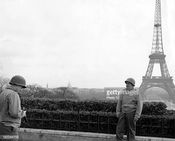 Direct from Aachen two US combat soldiers enjoy a 72hour pass and they photograph eachother in front of the Eiffel Tower in Paris February 5 1945