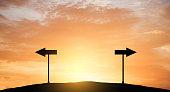 Direction arrow sign with sun light.
