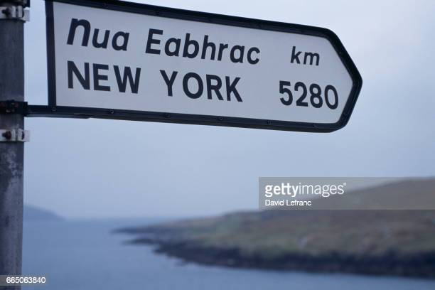 Direction sign indicates the distance to New York in both English and Gaelic on Beara Peninsula in County Cork Ireland | Location Garnish Point Beara...
