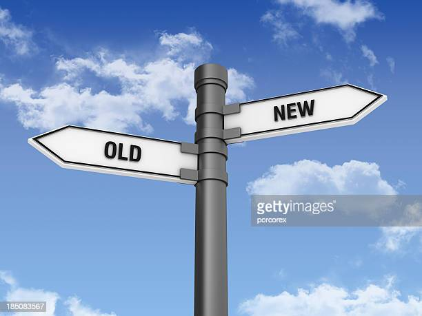 Directional Sign with OLD NEW Words and Sky