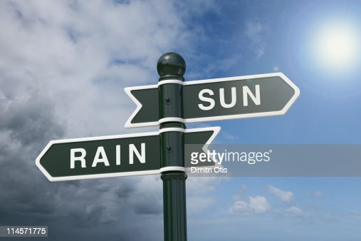 Directional signs pointing to rain and sunshine : Photo