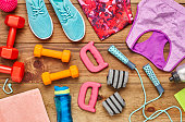 Directly above flat lay shot of various sports equipment. Dumbbells with jump rope  wristbands  shoes  water bottle  clothing  handles and towel are on hardwood floor. All are representing healthy lif