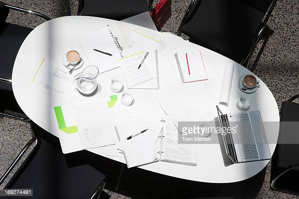 Directly above paperwork, coffee, laptops and notebooks on conference table