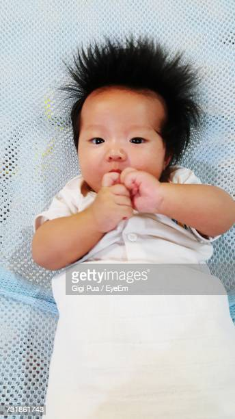 Directly Above Portrait Of Baby Lying On Bed