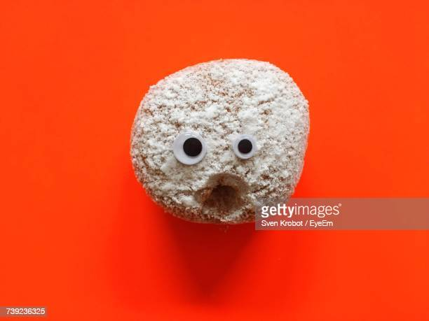 Directly Above Shot Of Anthropomorphic Face Made With Food On Orange Background