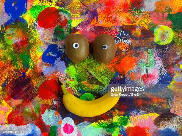 Directly Above Shot Of Anthropomorphic Face Made With Fruits On Colorful Table