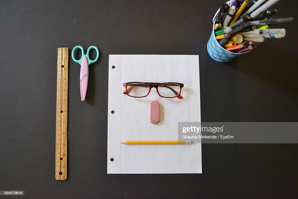 Directly Above Shot Of Anthropomorphic Face Made With Stationary On Table : Stock Photo