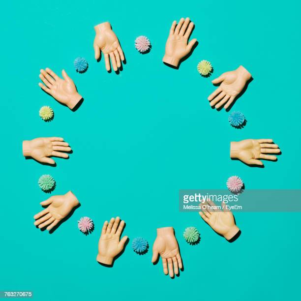 Directly Above Shot Of Artificial Hands On Turquoise Background