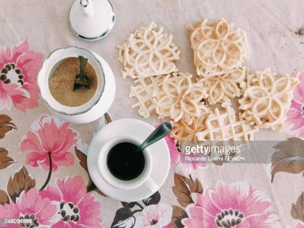 Directly Above Shot Of Black Coffee In Cup By Sweet Food On Table