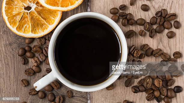 Directly Above Shot Of Black Coffee With Beans And Orange On Table