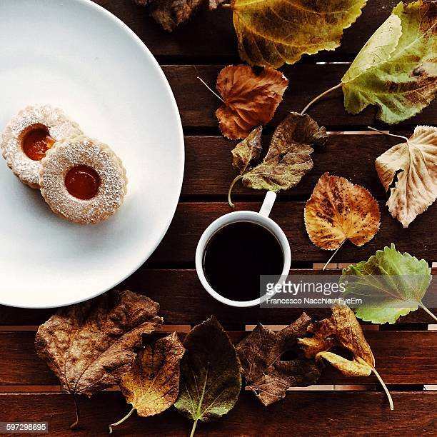 Directly Above Shot Of Black Coffee With Cookies And Dry Leaves On Table