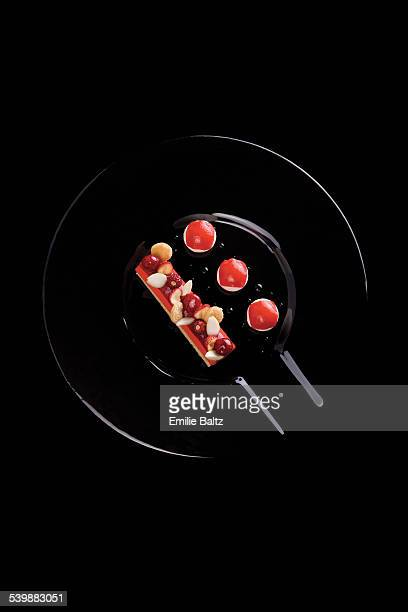 Directly above shot of cake garnished with berries on pan over black background