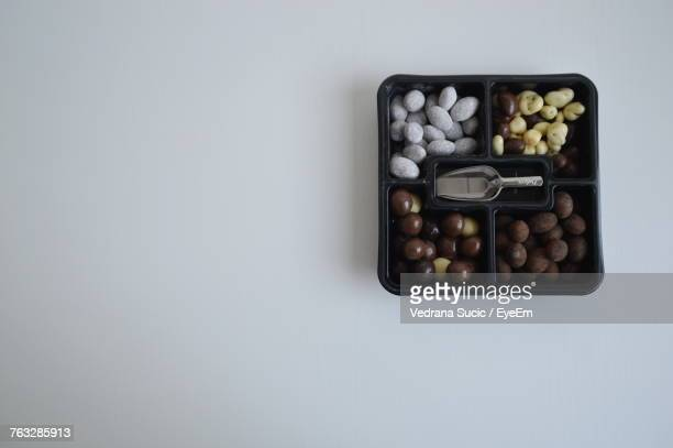 Directly Above Shot Of Candies In Container On White Background