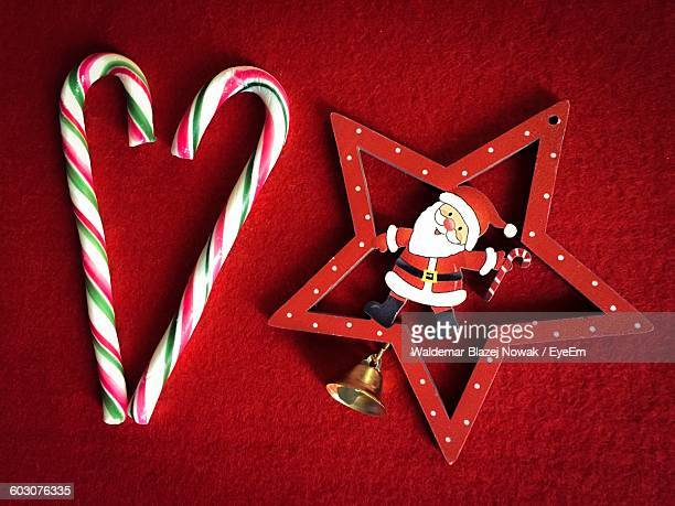 Directly Above Shot Of Candy Canes With Santa Christmas Decoration On Carpet