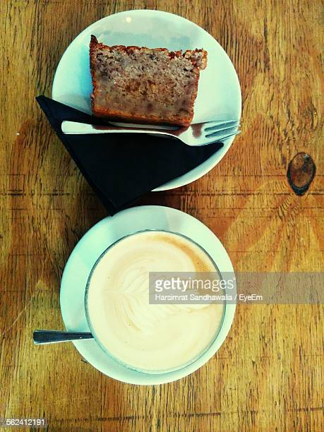 Directly Above Shot Of Cappuccino With Sliced Cake Served On Table