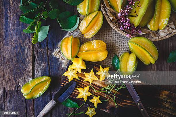 Directly Above Shot Of Carambola And Knife On Wooden Table