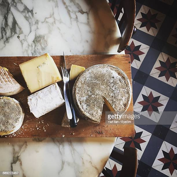 Directly Above Shot Of Cheese On Cutting Board At Table