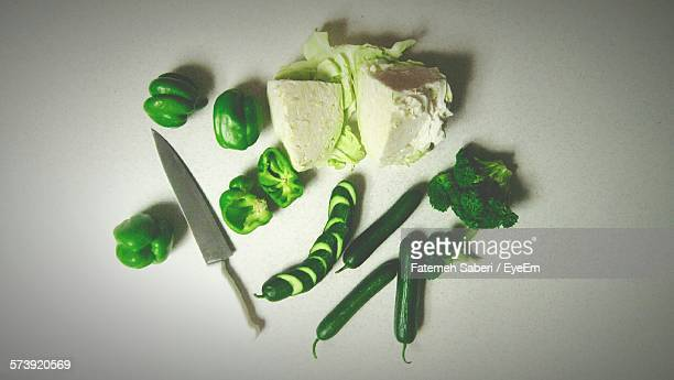 Directly Above Shot Of Chopped Vegetables And Kitchen Knife On White Background