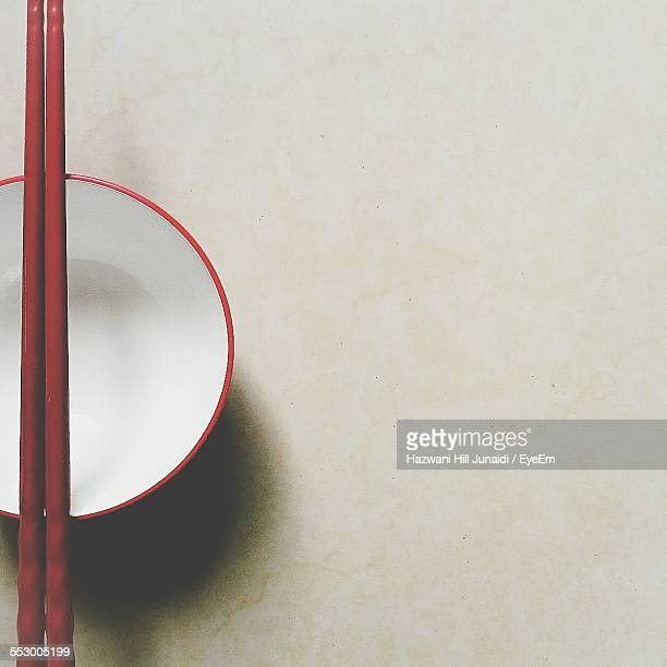 Directly Above Shot Of Chopsticks On Empty Bowl On Table