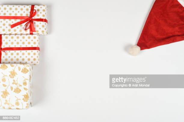 Directly above shot of Christmas gift boxes, Santa cap, white background copy area