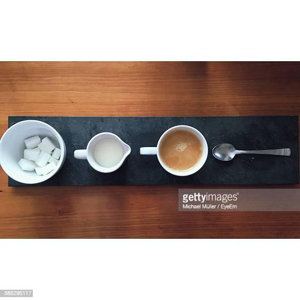 Directly Above Shot Of Coffee And Milk With Sugar On Wooden Table
