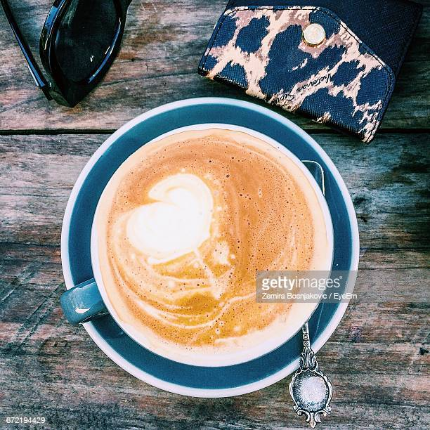 Directly Above Shot Of Coffee Cup By Wallet And Sunglasses On Wooden Table