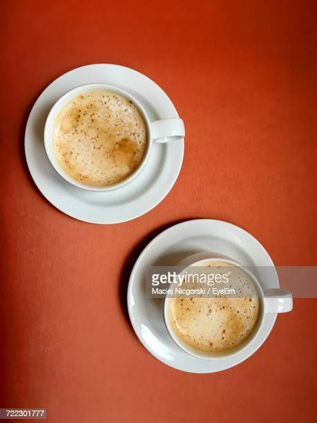 Directly Above Shot Of Coffee Cups Against Orange Background