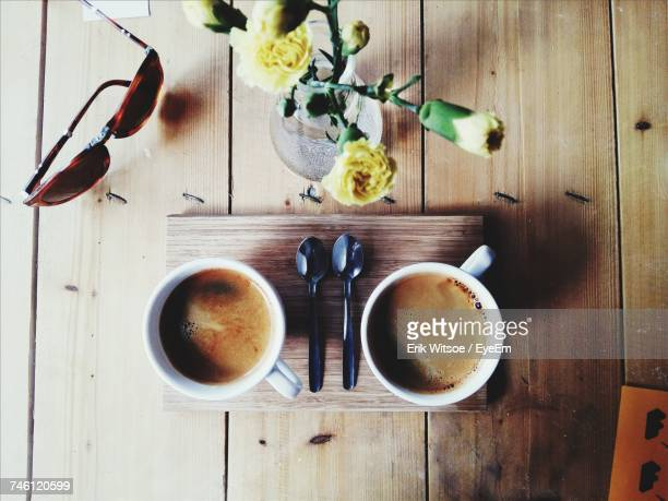 Directly Above Shot Of Coffee Cups With Flower Vase And Sunglasses On Table