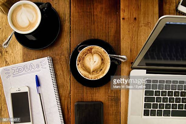Directly Above Shot Of Coffee Cups With Laptop By Smart Phone On Book