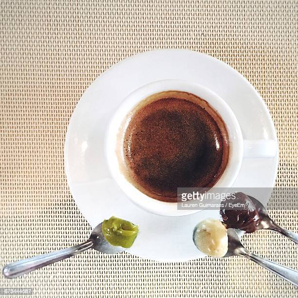 Directly Above Shot Of Coffee With Sweet Food In Spoons On Place Mat