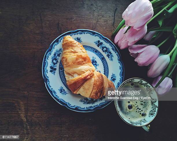 Directly Above Shot Of Croissant And Coffee With Pink Tulips On Table