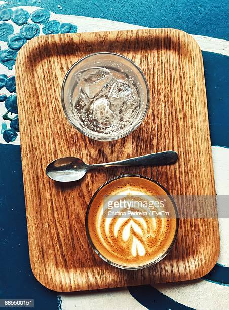 Directly Above Shot Of Drinking Glass By Cappuccino Served On Table