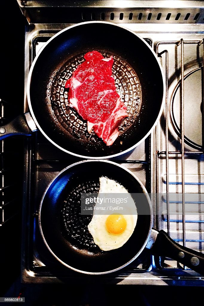 Directly Above Shot Of Egg White And Steak In Cooking Pan On Stove