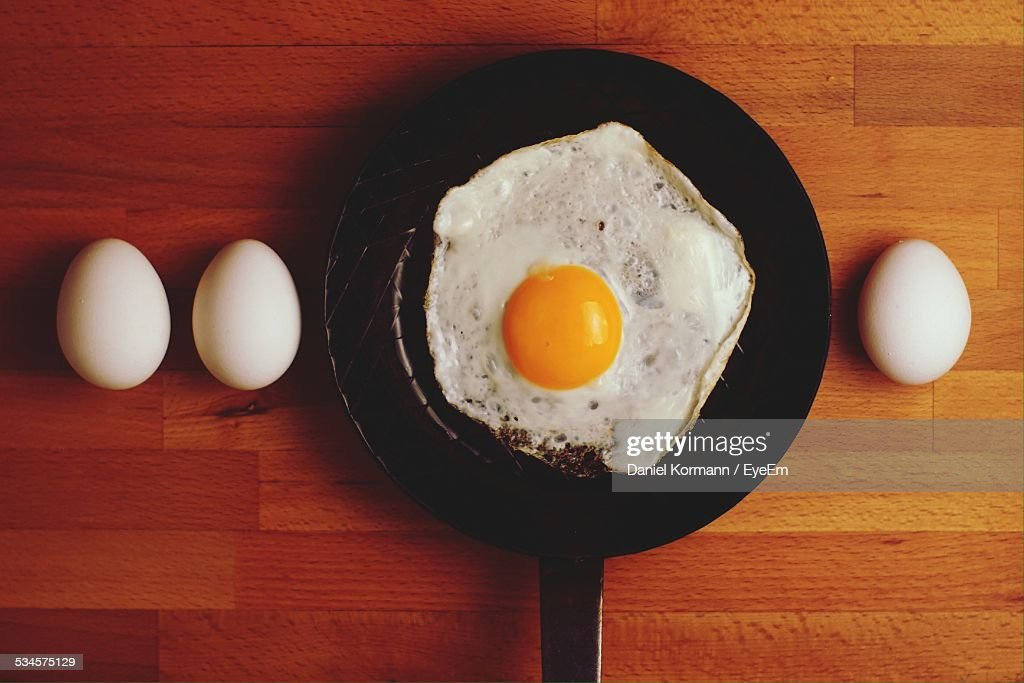 Directly Above Shot Of Eggs And Fried Egg In Frying Pan On Table