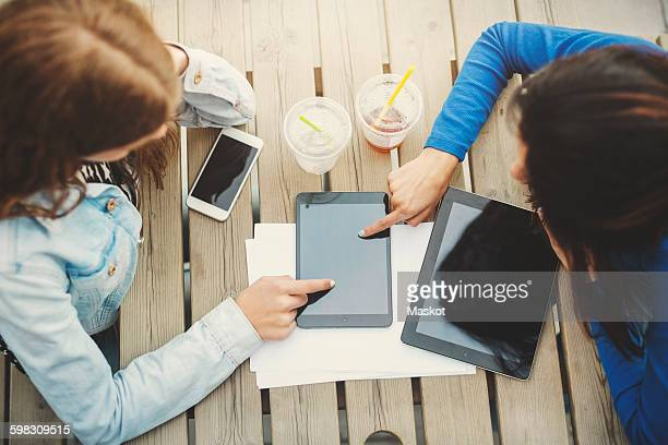 Directly above shot of female teenagers touching digital tablet at table