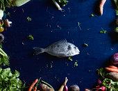 Directly above shot of fish amidst vegetables on blue table