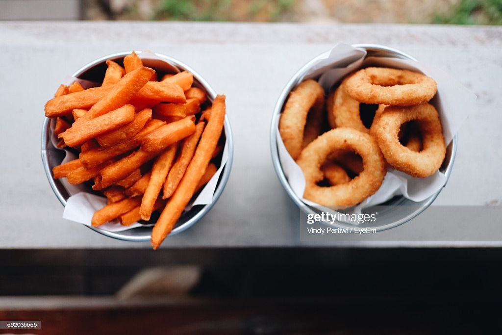 Directly Above Shot Of French Fries And Onion Rings In Bowls On Window Sill