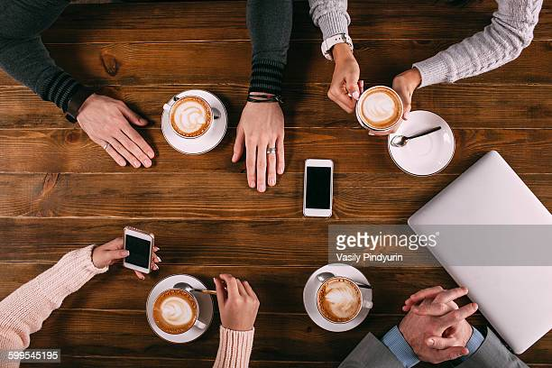 Directly above shot of friends having coffee at wooden table in cafe