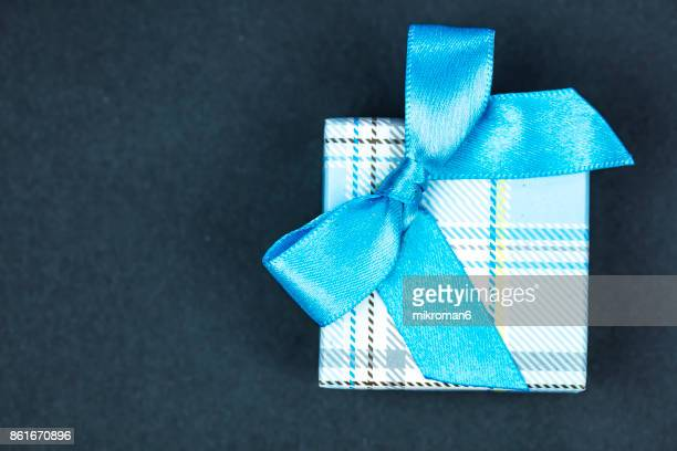 Directly Above Shot Of Gift Box With blue Ribbon on black background