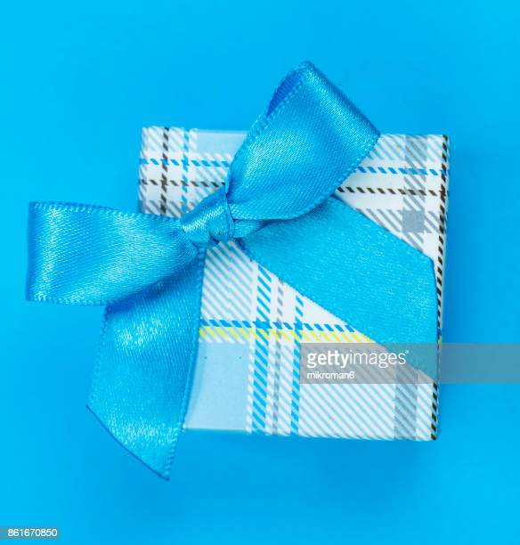 Directly Above Shot Of Gift Box With blue Ribbon on blue background