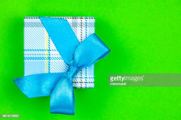 Directly Above Shot Of Gift Box With blue Ribbon on green background