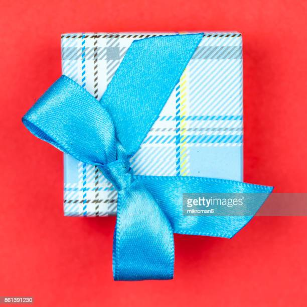 Directly Above Shot Of Gift Box With blue Ribbon on red background