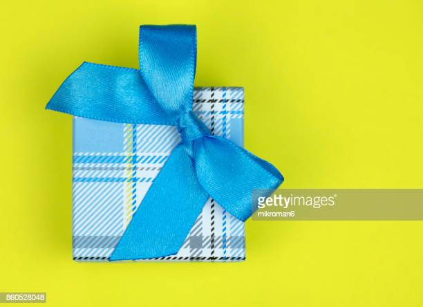 Directly Above Shot Of Gift Box With blue Ribbon on yellow background
