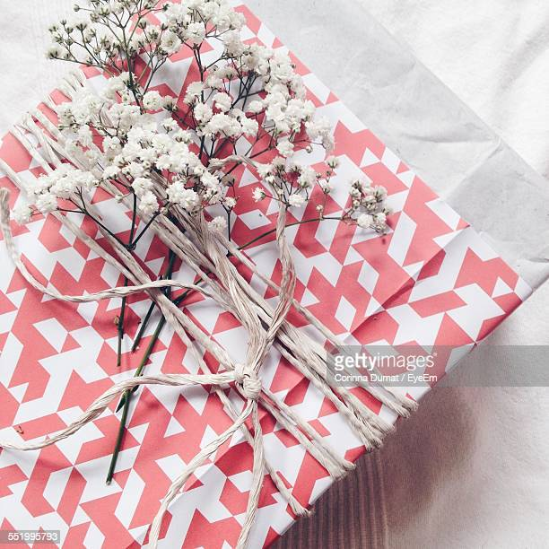 Directly Above Shot Of Gift Box Wrapped In Paper With White Flower