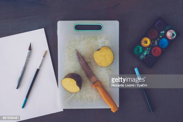 Directly Above Shot Of Halved Potato And Knife On Cutting Board By Painting Equipment