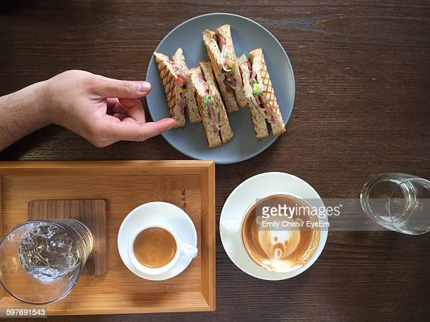 Directly Above Shot Of Hand And Sandwich On Table