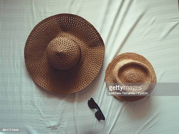 Directly Above Shot Of Hats And Sunglasses On Bed