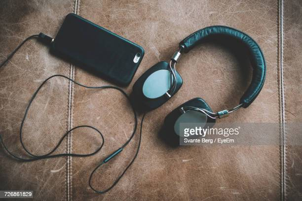 Directly Above Shot Of Headphones And Mobile Phone On Seat